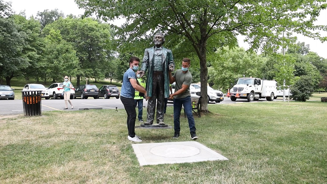 John Boedicker, left, and Charles Milks carry a Frederick Douglass statute made by sculptor Olivia Kim to its base at Kelsey's Landing in Maplewood Park. - PHOTO BY MAX SCHULTE