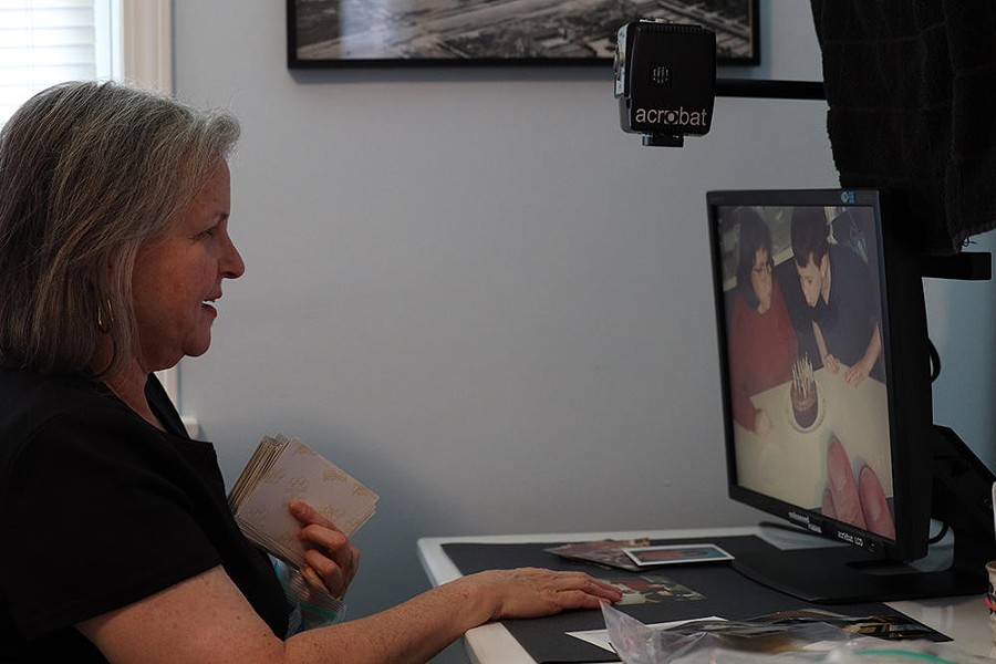Patty Starr uses a magnifier to edit and digitize family photos — a project that helps her cope with being at home for days at a time. - PHOTO CREDIT MAX SCHULTE