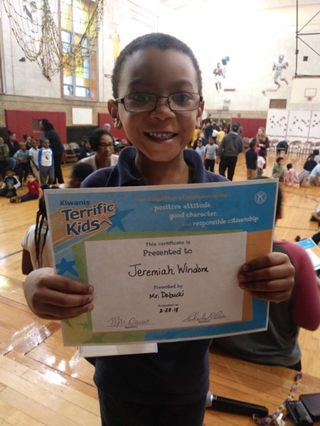 Windom's 8-year-old son, Jeremiah, holds up an award for positive attitude, good character, and responsible citizenship. - PHOTO PROVIDED