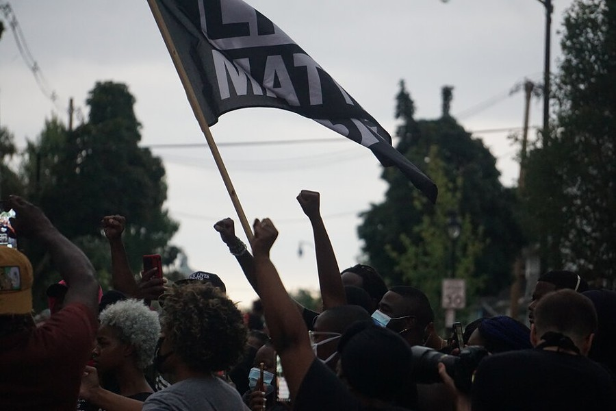 Protesters wave a Black Lives Matter flag on Jefferson Avenue. - PHOTO BY GINO FANELLI