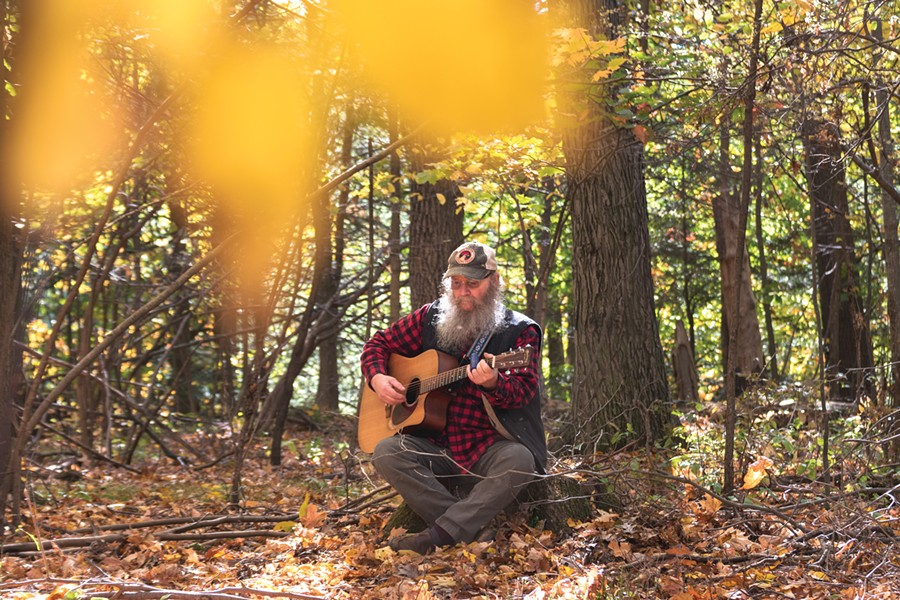 Bob Bunce plays the guitar on his rural property near Groveland, New York. - PHOTO BY RYAN WILLIAMSON