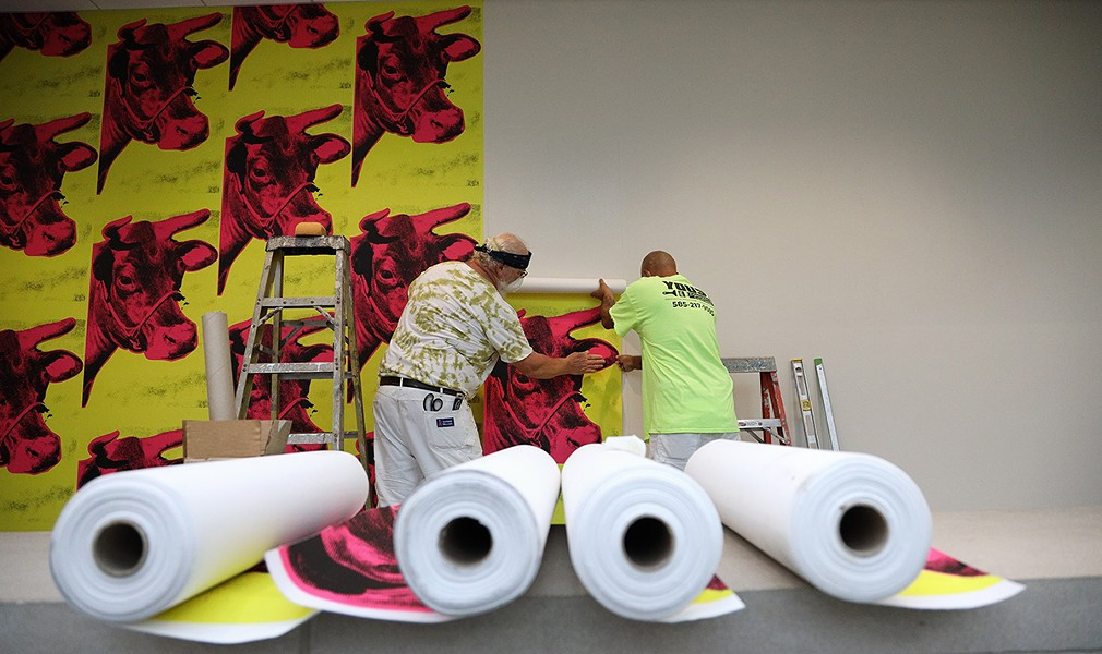 "Workers at the Memorial Art Gallery hang cow wallpaper that is part of the ""Season of Warhol"" exhibit. - PHOTO BY MAX SCHULTE"