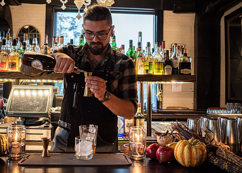"""The Revelry's bar manager Mack Hartman adds the clove and brown sugar syrup to """"The Iron Sickle."""" - PHOTO BY JACOB WALSH"""