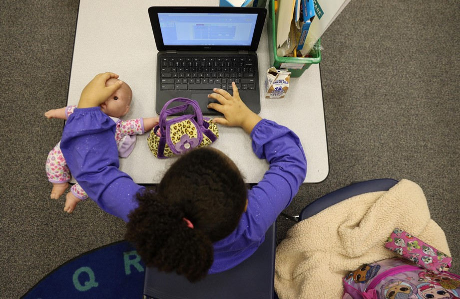 Alianna Lee and her doll Sophie log into her next class after finishing lunch. Kids eat at their desks and then teacher's aides disinfect the work areas. - PHOTO BY MAX SCHULTE / WXXI NEWS