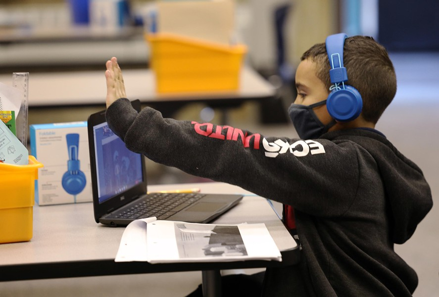 Dante Flores gives his class a virtual high-five after completing a discussion about a story his class read. - PHOTO BY MAX SCHULTE / WXXI NEWS