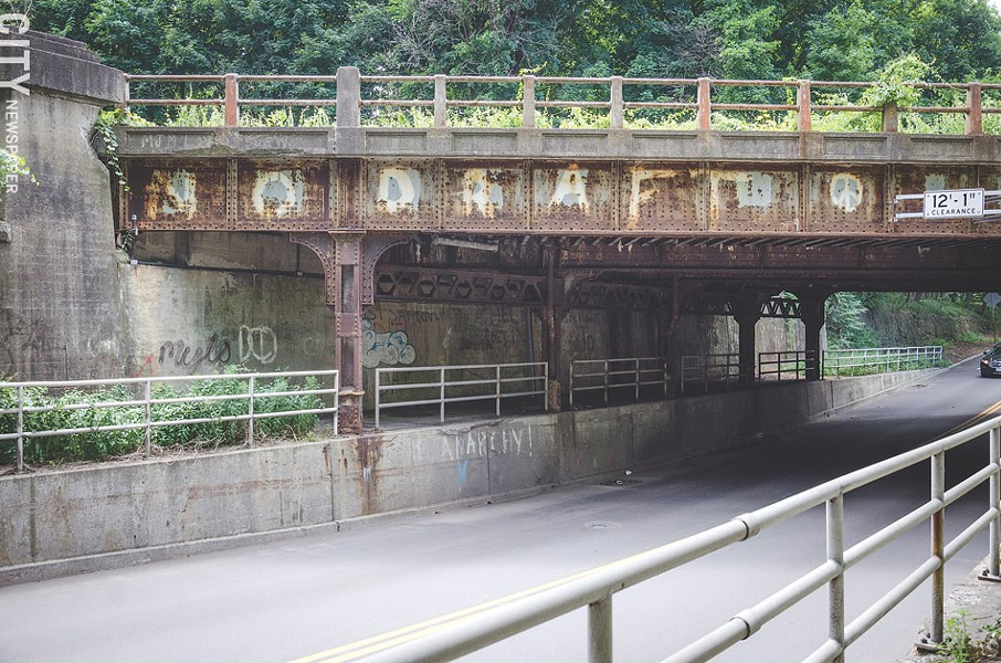 Graffiti created by a group of friends in 1981 to protest the reinstatement of draft registration has remained on the CSX bridge that passes above Penfield Road in Brighton. - PHOTO BY MARK CHAMBERLAIN