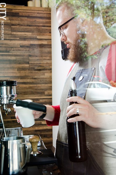 Meraki Coffee Co. owner Ryan Baker works the espresso bar at Cheesy Eddie's, where his pop-up company offers such signature concoctions as the Salted Nutella Latte and a carbonated iced espresso beverage made with Fizz Cola. - PHOTO BY MARK CHAMBERLIN