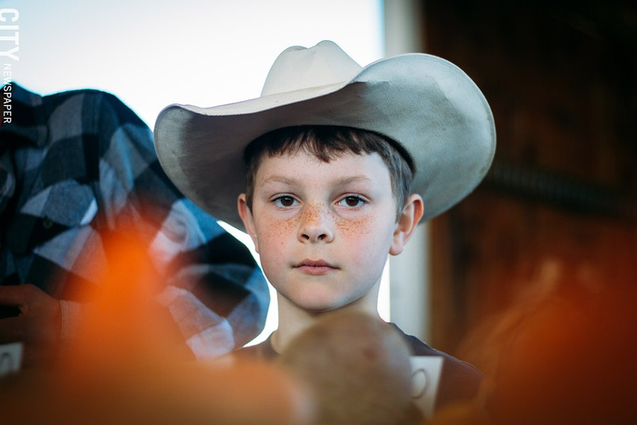 "Lucas Welker, who is 7 years old, and his 12-year-old cousin Abraham Amsler both live in Walworth and help operate the Amsler family farm, Oldhome Farm. - Lucas gets up at 6 a.m. to make it to the market for what he calls the ""second shift."" Abraham has to get up at 2:30. Lucas and Abraham finished their chores in the dairy barn, which included milking cows, around 10 p.m. the night before. ""You get to help out and people get the stuff they need."" - PHOTO BY KEVIN FULLER"