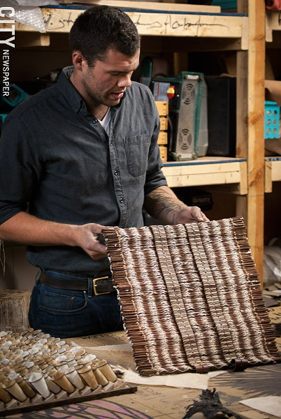 Kinz-Thompson with his deconstructed book sculptural wall pieces in his Hungerford studio. - PHOTO BY RYAN WILLIAMSON