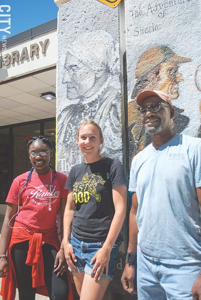 Ebony Singleton, Chloe Smith, and Futch in front of their work at the Arnett Branch Library. - PHOTO BY JACOB WALSH