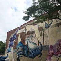 "WALL\THERAPY 2017: getting started Sarah Rutherford has made a lot of progress on her massive West Main Street mural for WALL\THERAPY, which is also part of Rutherford's ""Her Voice Carries"" project. PHOTO BY REBECCA RAFFERTY"