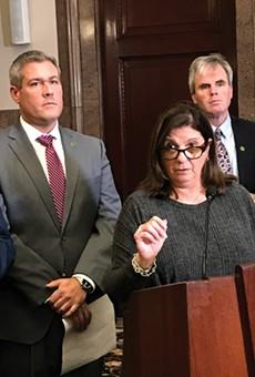"Republican Monroe County Legislator Karla Boyce explains her decision to vote to repeal the ""police annoyance"" law she sponsored months ago, as  Monroe County Executive Adam Bello, left, and Democratic Legislator John Baynes look on."