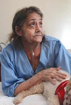 Linda Barger sits in the bed of her Sherman Street apartment with her dog, Bear, on January 16.