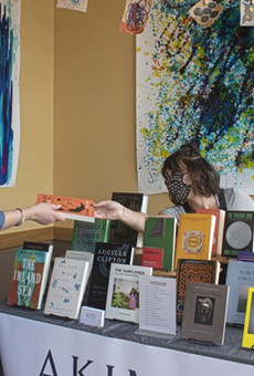Rachel Crawford (right) of Akimbo Books with a customer at a recent pop-up event at John's Tex Mex.