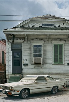 """After the floods receeded, watermarks stain a car and houses in post-Katrina New Orleans. This photograph is part of """"Robert Polidori: Chronophagia,"""" which is on view at the Memorial Art Gallery through July 24."""