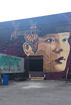 Jess X Snow's finished mural for WALL\THERAPY 2017, on the lot-facing wall at 936 Exchange Street. On the truck is an in-progress piece by Cruk FUA.