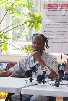 Christopher Pate (center) with his mother and the Rev. Lewis Stewart at a news conference in early August.