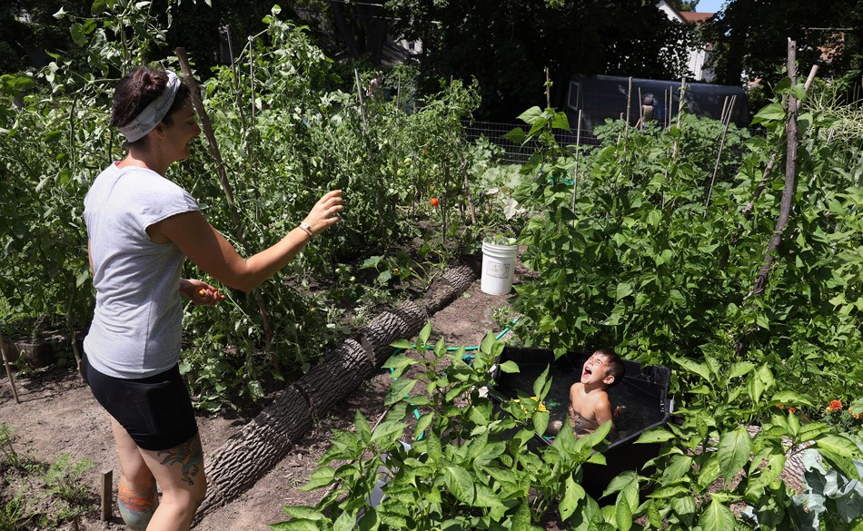 Sarah Spano, who lives on Exchange Street, tosses a sungold tomato from her garden to her son, Arlo. - PHOTO BY MAX SCHULTE