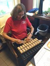 Margaret O'Neill, program director of the Friends of the Rochester Public Market, helps customers exchange SNAP benefits for wooden tokens they can spend at the market.