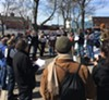Justin Delinois, an organizer with UR DREAMers, addresses a crowd of about 40 people outside of the Rochester Greyhound and New York Trailways station.