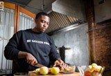 PHOTO BY MARK CHAMBERLIN - Calvin Eaton, who created the Gluten Free Chef blog, prepares food in the kitchen of his new community center, 540WMain. Eaton wants to use the space for art, culinary, and educational programs for Rochester youth, and to promote the Susan B. Anthony Neighborhood.