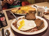 PHOTO BY JACOB WALSH - The homemade corned beef hash with over-easy eggs and - pumpernickel toast (front) and Artist's omelet (back) at Jim's at The Mall.