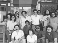 1985 Guadalupe Cultural Arts Center staff in front of the Guadalupe Theater; Back row (left to right): Sandra Cisneros, Patricia Montoya, Jorge Pina, David Mercado Gonzales with son Rafael Gonzales, Rolando Mazuca, Paul Colorado, Jose Garza and Max Martinez; Front row (left to right): Eduardo Diaz, Felice Garcia, Juan Tejeda and unidentified persone
