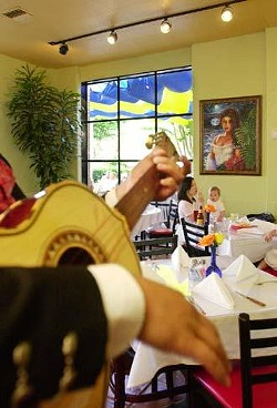 A mariachi musician plays in one of the brightly lit dining areas of SoLuna. The restaurant, located in the trendy Collection shopping center, features live music Wednesday through Sunday evenings.