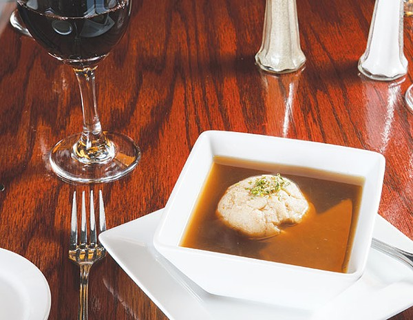 A single dumpling floats atop an honest bouillon soup. - WWW.PAYTONPHOTOGRAPHY.COM