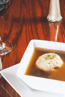 A single dumpling floats atop an honest bouillon soup.