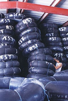 Angel Gomez of New Braunfels pulls down a tower of inner tubes for customers headed to the river.