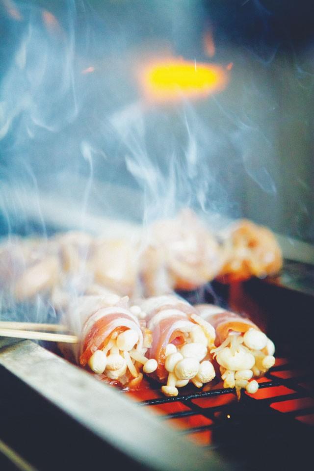 Bacon-wrapped enoki cooking on Izakaya Nin's robata grill. - JOSH HUSKIN