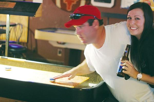 Brittany Magott gets a shuffleboard lesson from Rob Bracken at Sir Winston's Pub. - CHUCK KERR