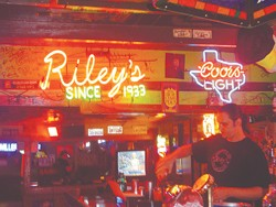 Chris Meekes tends bar under the neon lights at Riley's Tavern.