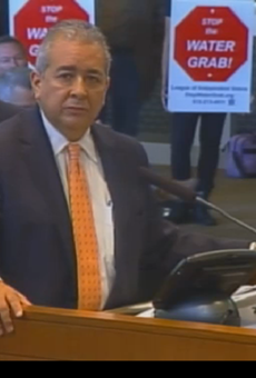 This screen grab of a City Council meeting shows San Antonio Water System President and CEO Robert Puente answering questions as protestors stand behind him.