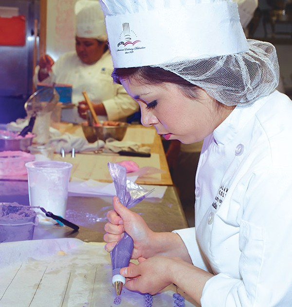 Claudia Treviño practices piping in her cake decorating class. - ESSENTIALS210