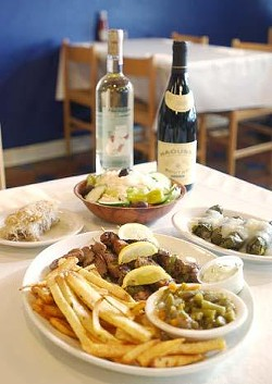 Clockwise from front - combination plate with beef, lamb and pork souvlaki, gyro meat, french fries, green beans, greek salad, and a side of tzatziki; homemade walnut filled kataifi; Greek salad and an order of hot Dolmades - ground beef, rice, and spices wrapped in grape leaves and topped with an egg lemon sauce.