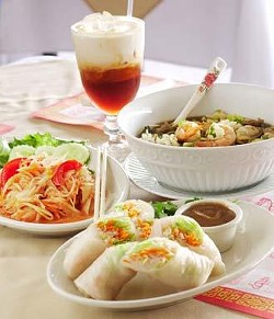 Clockwise from front: Thai summer rolls with special dipping sauce, green papaya salad, Thai iced tea, and a bowl of Jasmin noodle soup.