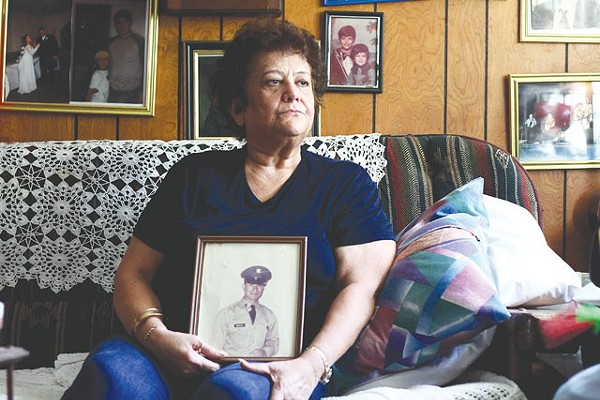 Decades of struggle: Diana Quintanilla Montoya holds a photo of her husband. - MICHAEL BARAJAS