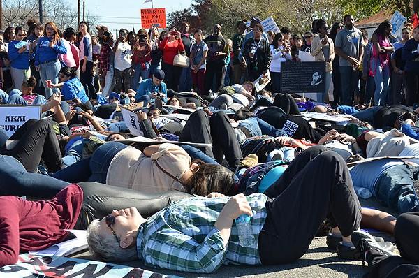 "Dozens of activists staged a ""die-in"" at the city's MLK March. - ALBERT SALAZAR"