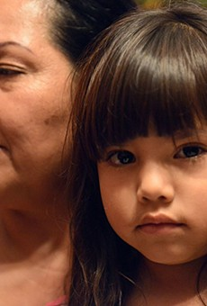 Erica Alvarado's daughter looks on while in the arms of her grandmother.