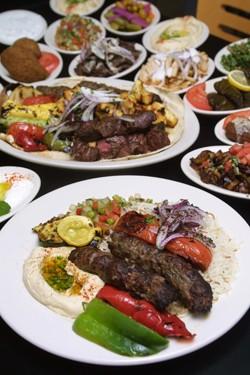 Jerusalem Grill's kafta kabob served with grilled vegetable rice and salad garnish.