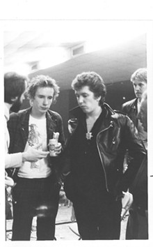 Johnny Rotten and Steve Jones listening to unidentified man