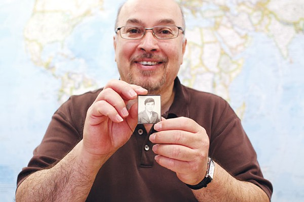 Libyan dissident Mansour El-Kikhia holding a photo of himself from before he fled his hometown of Benghazi 30 years ago. - MICHAEL BARAJAS
