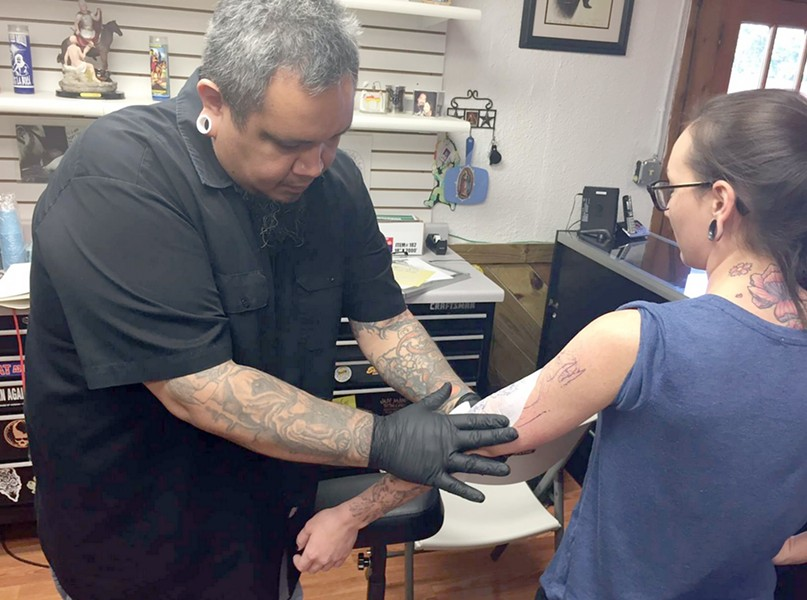 "Orlando-based tattoo artist Rick Rosas transfers an image on a client at Los Muertos Tattoo Company in the Medical Center. Rosas was left without a place to work when the final day of the Texas Tattoo Jam was cancelled after promoter Renee ""Red"" Neilson failed to pay the San Antonio Event Center for renting the venue. Los Muertos owner Lupe Diaz Jr. opened his shop to Rosas to help him recoup some of his losses. - KIKO MARTINEZ"
