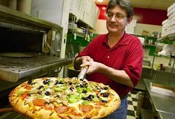 """Owner and manager Terry Basore takes a piping hot medium """"""""Mama Mia"""""""" pizza out of the oven at Pizza Italia. The Mama Mia features pepperoni, Italian sausage, beef, black olives, mushrooms, onions, green peppers, and jalapeÒos."""