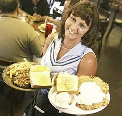 Stock Yards Cafe waitress Lillie Aldrich lifts orders of chicken fried steak with mashed potatoes and green beans and a bacon-cheese-chopped steak with fries and mac and cheese.