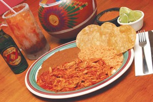 Tinga de pollo en tostadas, served hot with rice, beans, and a cold Dos Equis at Guajillo's.
