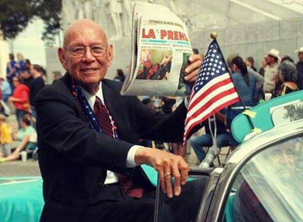 Tino Duran shows off a copy of La Prensa while participating in a Fiesta parade. - COURTESY