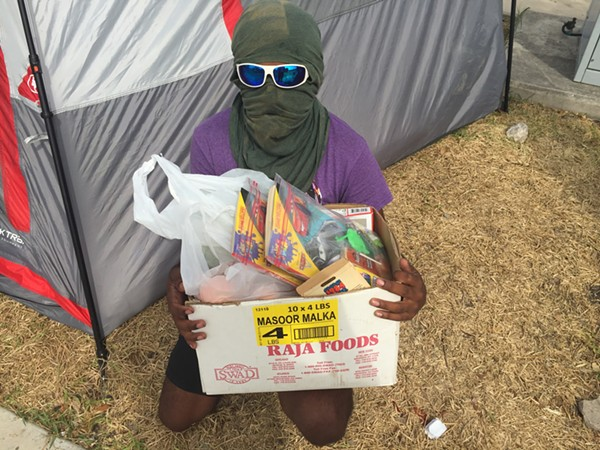 """Occupy ICE San Antonio spokesman """"Kazi"""" shows off a box of food and activity books the group gives out to people entering San Antonio's ICE detention facility. - SANFORD NOWLIN"""